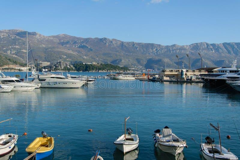 被停泊的渔船美丽的景色在地中海城市布德瓦,黑山小游艇船坞港口  风景山背景 免版税库存照片