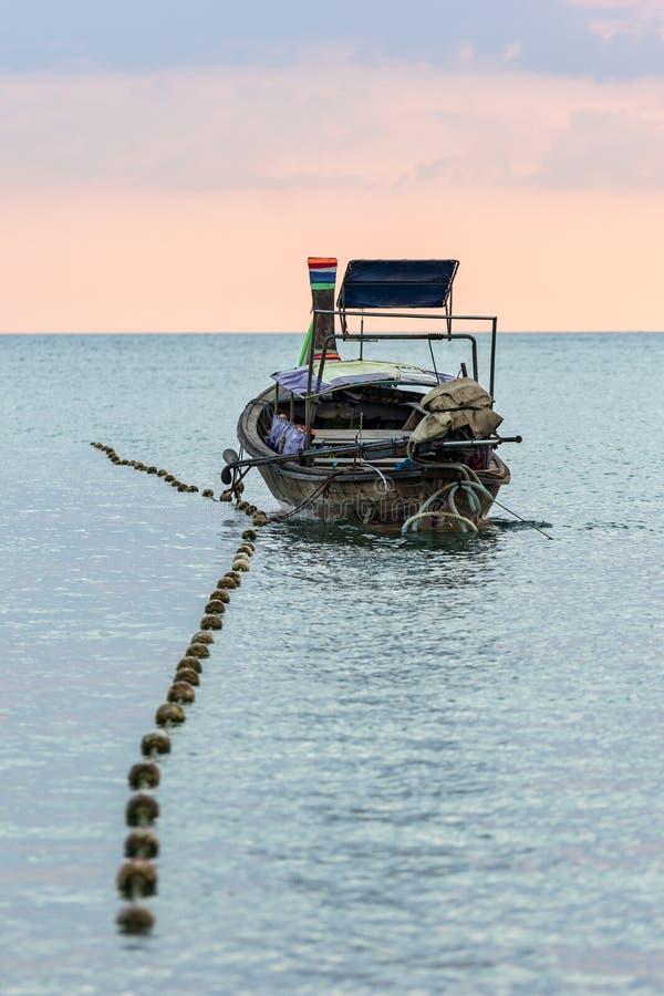 被停泊的长尾巴泰国小船在风平浪静水中在晚上 库存照片