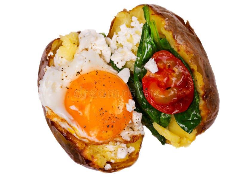 被充塞的土豆用鸡蛋、乳酪、菠菜和蕃茄 查出在白色 看法从上面,顶面演播室射击 免版税库存照片
