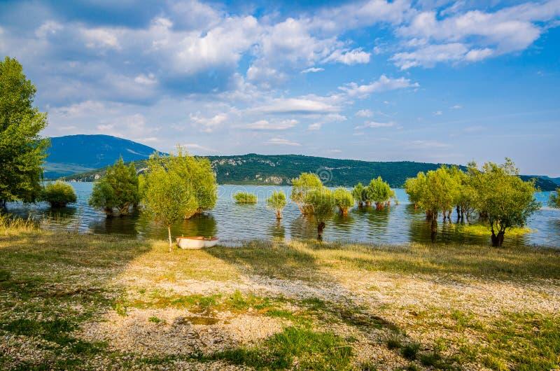 被充斥的树和小船在岸在湖Sainte克鲁瓦在村庄Sainte克鲁瓦du维尔东,法国 免版税图库摄影