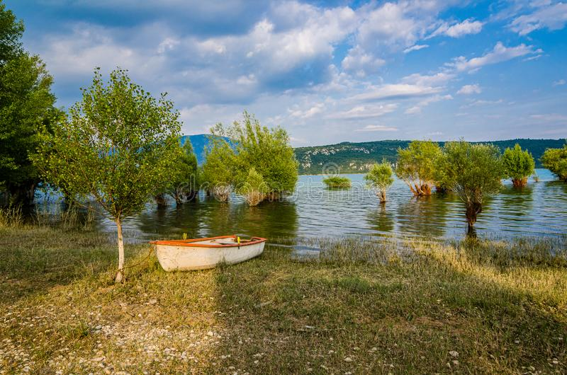 被充斥的树和小船在岸在湖Sainte克鲁瓦在村庄Sainte克鲁瓦du维尔东,法国 库存图片