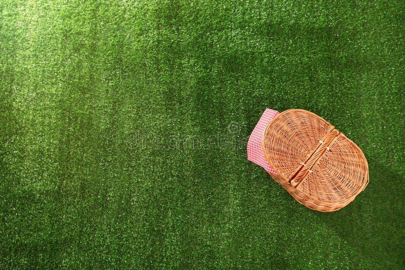 被关闭的野餐篮子和餐巾在草,空间文本的 库存照片