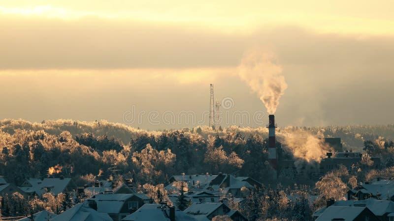 被冰的树、多雪的屋顶和烟斗在日落轻率冒险 免版税库存照片