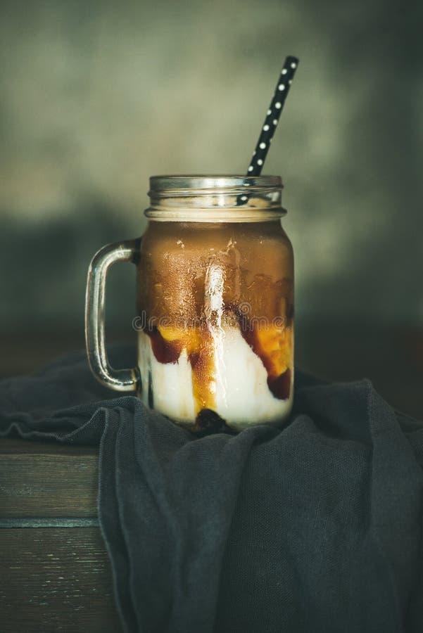 被冰的焦糖macciato咖啡用在瓶子的牛奶 库存图片