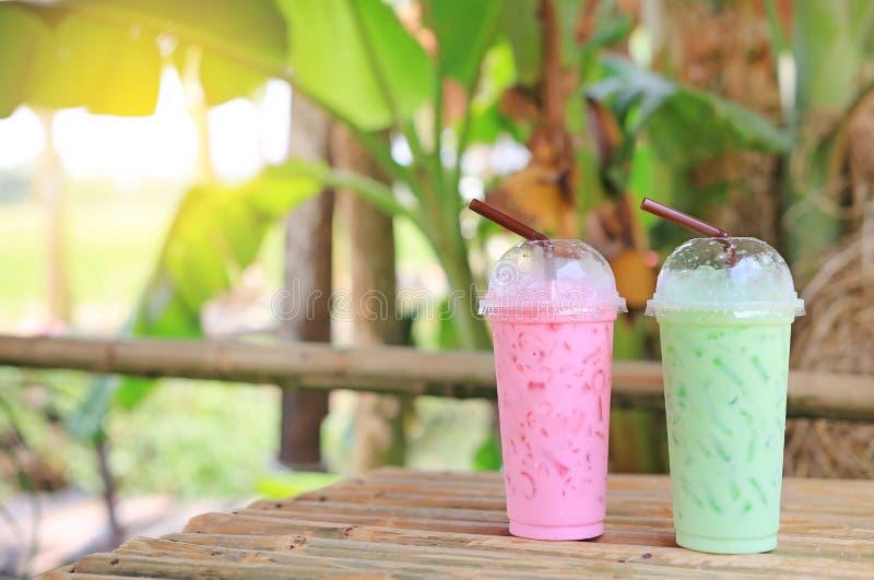被冰的绿茶matcha拿铁和汁液桃红色草莓牛奶为在竹木桌投入的夏天反对自然背景 免版税库存照片