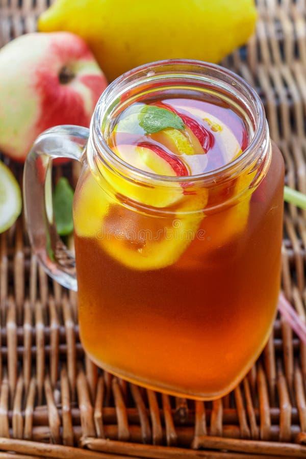 被冰的茶用柠檬和瓶子在桃子螺盖玻璃瓶.美食,桃子.金属自然车图片