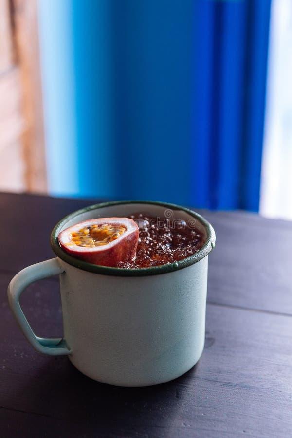 被冰的西番莲果汁在有裁减一半的锌杯子服务新鲜的西番莲果 库存图片