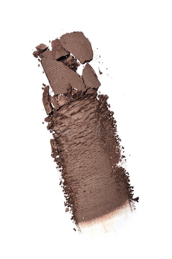 被击碎的棕色眼影膏污迹作为化妆产品样品的  图库摄影