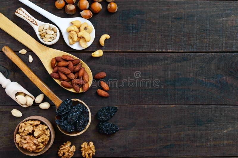 被分类的不同的坚果,修剪,在匙子的南瓜籽在黑暗的木背景 免版税库存照片