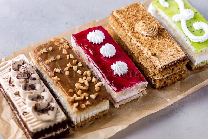 被分类的不同的微型蛋糕用奶油色咖啡巧克力盐溶了焦糖和莓果在水平的鲜美微型蛋糕点心上 图库摄影
