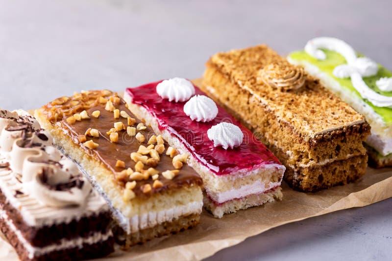 被分类的不同的微型蛋糕用奶油色咖啡巧克力盐溶了焦糖和莓果在水平的鲜美微型蛋糕点心上 库存照片