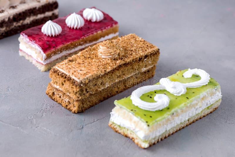 被分类的不同的微型蛋糕用奶油色咖啡巧克力盐溶了焦糖和莓果在水平的鲜美微型蛋糕点心上 免版税库存图片