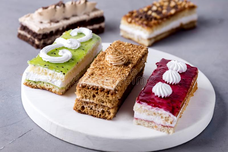 被分类的不同的微型蛋糕用奶油色咖啡巧克力盐溶了焦糖和莓果在水平的鲜美微型蛋糕点心上 免版税库存照片
