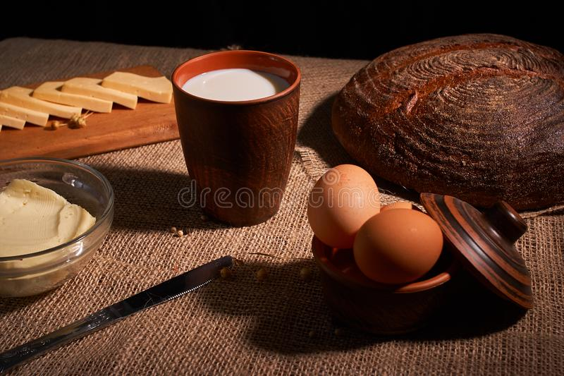 被分类的乳制品挤奶,乳酪,在桌上的黄油土气静物画 库存图片