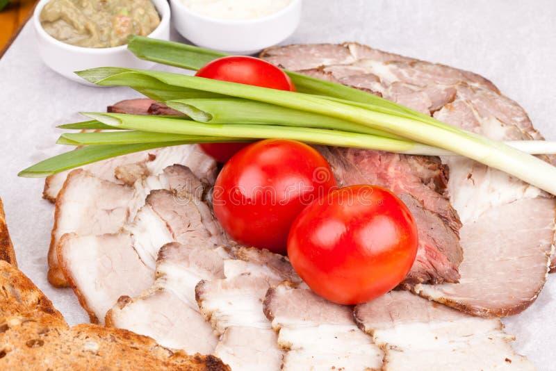 被分类的冷盘用敬酒的面包、西红柿、葱和调味汁在白色板材 免版税库存照片
