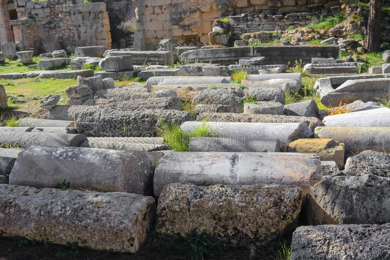被分类的古老考古学柱子在地面上排队了在科林斯湾希腊-选择聚焦 免版税库存照片