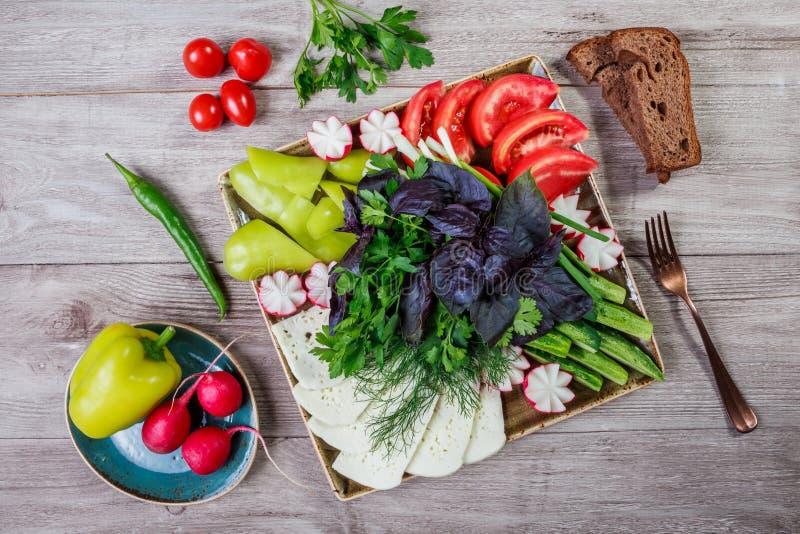 被分类的新鲜蔬菜和希腊白软干酪盛肉盘在轻的木背景 免版税图库摄影