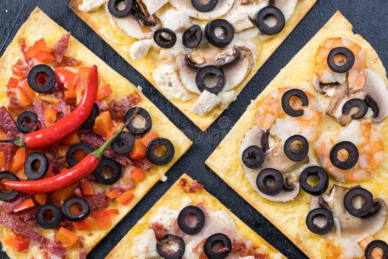 什锦披萨片 玛格丽塔,意大利香肠,四份奶酪披萨 顶视图 在有纹理的老年人身上 库存照片