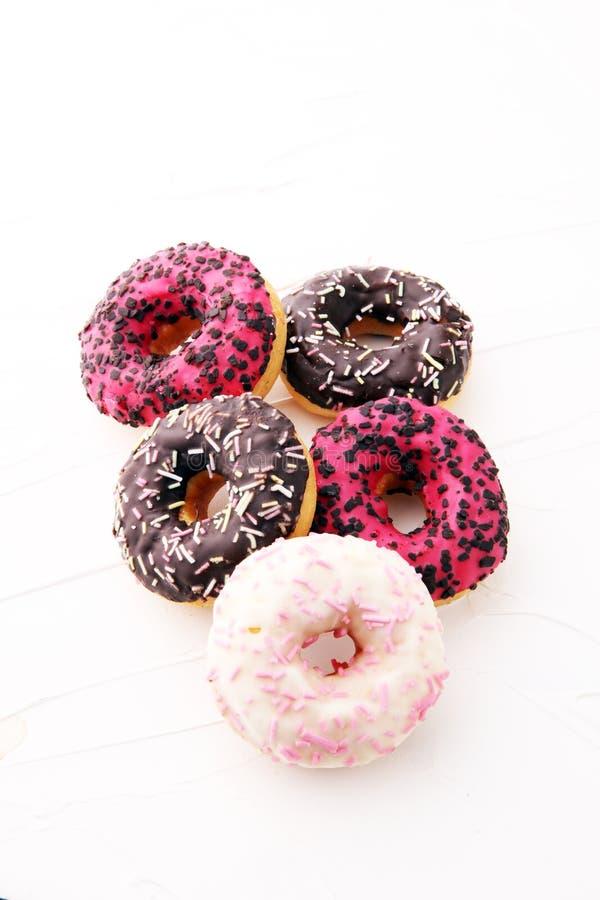 被分类的油炸圈饼用结霜的巧克力,变粉红色给上釉并且洒 库存图片