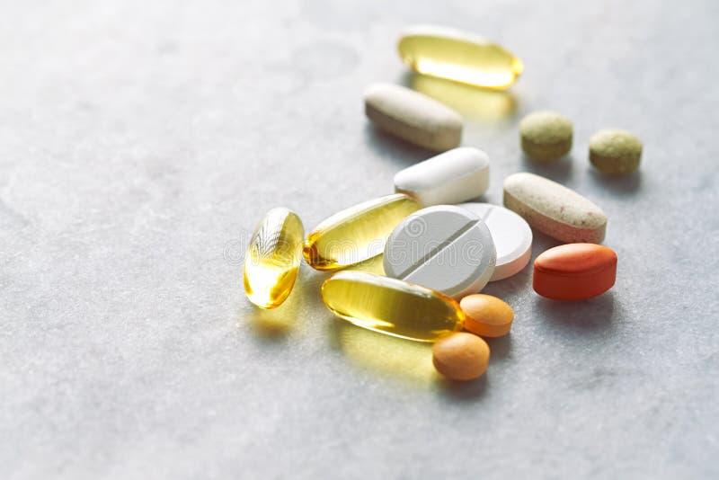 被分类的自然膳食补充剂和维生素在灰色背景 免版税库存图片
