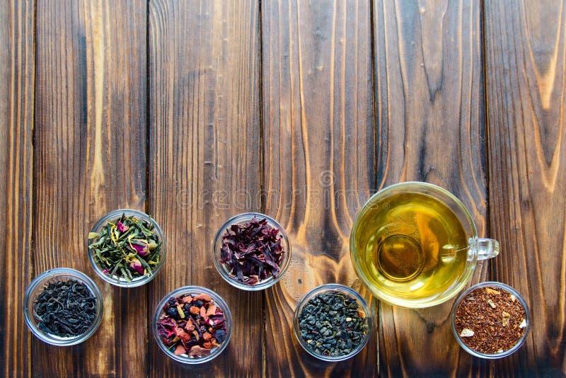 被分类的茶的选择在透明小的碗的在自然本底 免版税库存照片
