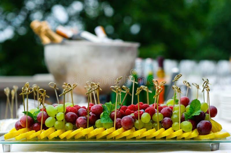 被分类的新鲜水果盛肉盘在自助餐桌上 免版税库存图片