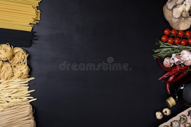 被分类的面团用鸡蛋、蘑菇和意大利烹调成份在黑背景 顶视图,拷贝空间 免版税库存照片