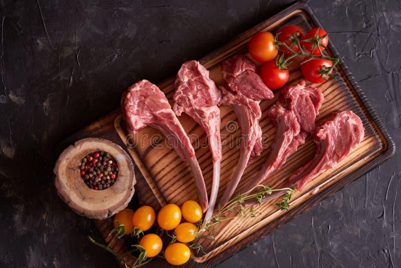 被切开的未加工的放在架子上的羊羔在一个切口木板的用黄色和红色蕃茄,五颜六色的豌豆,在石黑暗的背景 图库摄影