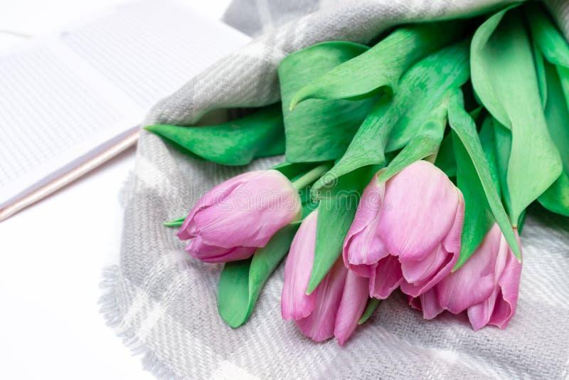 被切开的桃红色淡紫色郁金香花束与一个笔记本的在白色背景关闭 库存照片