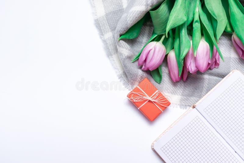 被切开的桃红色淡紫色郁金香花束与一个红色礼物盒和笔记本的在与拷贝空间关闭的白色背景 库存照片