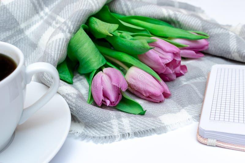 被切开的桃红色淡紫色郁金香花束与一杯咖啡的和笔记本关闭 图库摄影
