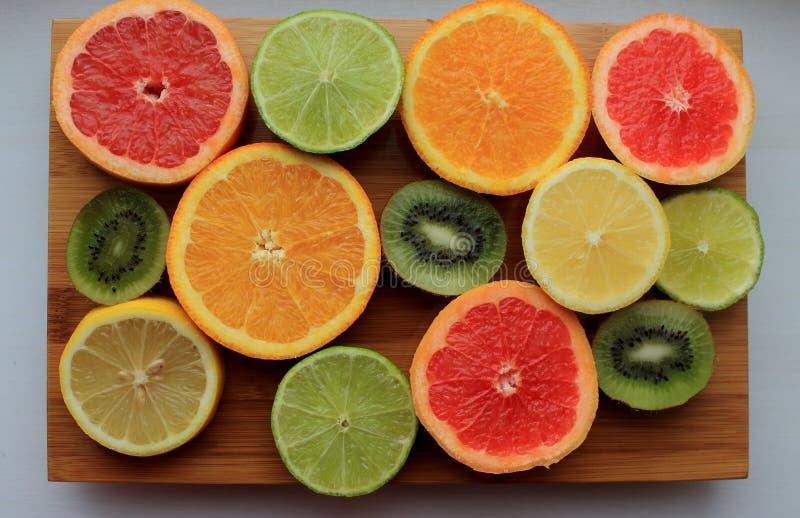 被切的五颜六色的柑橘水果顶视图的混合 在木板的桔子、柠檬、猕猴桃、葡萄柚和石灰半切片 免版税库存图片