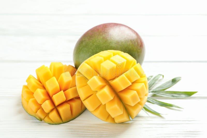 被切的成熟芒果和棕榈叶在白色背景 免版税库存照片