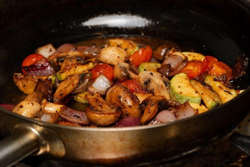 被切的菜用白色蘑菇,夏南瓜,西红柿,红洋葱 烹调在煎锅,极端接近的素食主义者盘 免版税库存照片