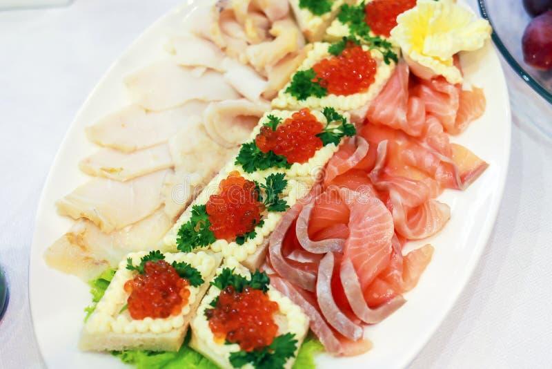 被切的鱼和被烘烤的篮子用红色鱼子酱在一块板材在餐馆 库存图片