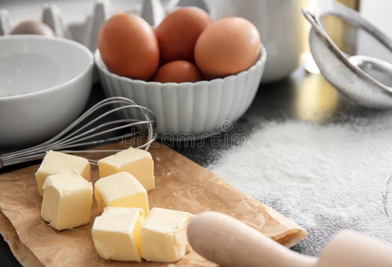 被切的黄油、飞奔和鸡蛋在厨房用桌上 面包店车间 免版税库存图片