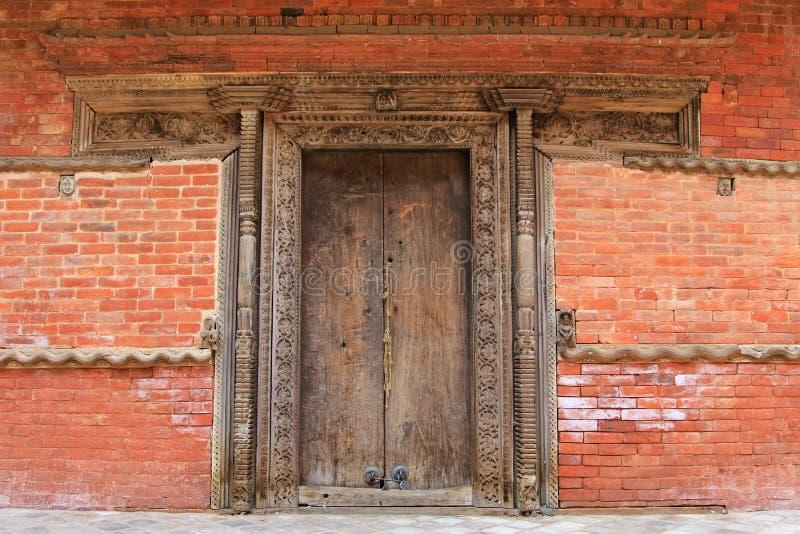 被制作的木门框和墙壁装饰在加德满都,尼泊尔 免版税库存照片