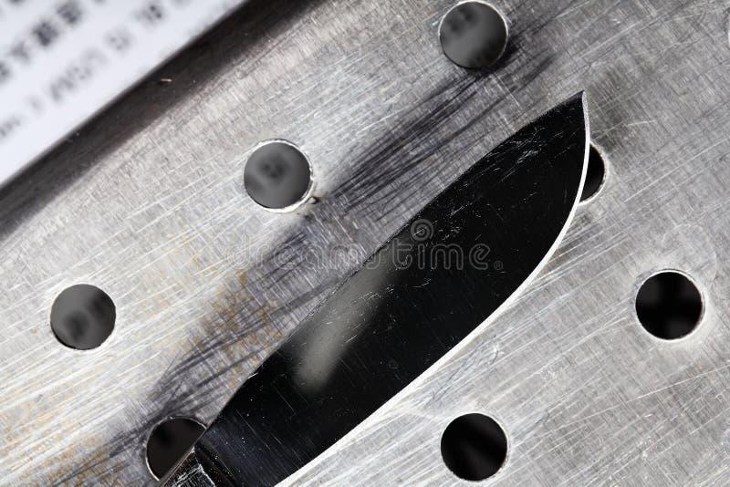 被刺穿的金属表面上的刀子 免版税库存照片