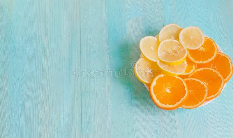 被削减的切片桔子和柠檬在一块板材在一个蓝色木背景特写镜头 概念健康维生素素食主义者食物 库存照片