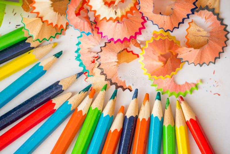 被削尖的颜色铅笔和铅笔削片,一个孩子的手白色背景的 图库摄影