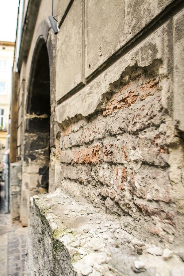 被剥皮的砖墙在有门曲拱的古老的议院里 库存照片