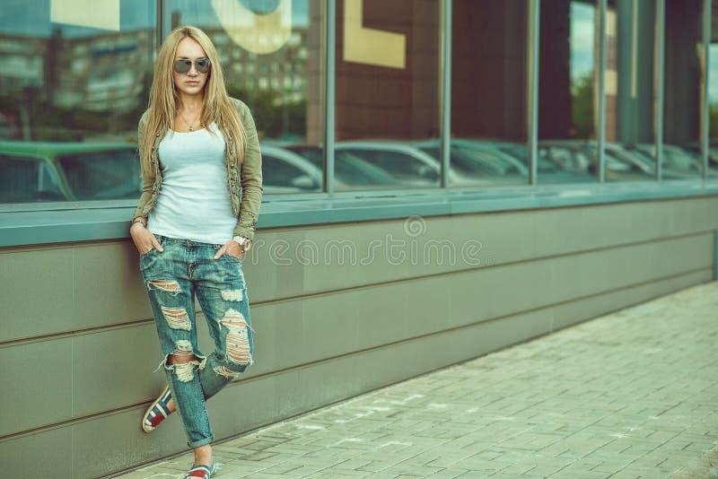 被剥去的牛仔裤的时髦的少妇在城市购物中心前面 库存照片
