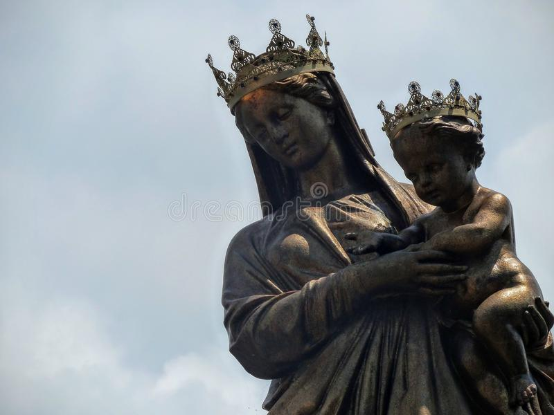被加冠的圣母玛丽亚的古铜色雕象有基督孩子的有天空的在背景中 免版税库存图片
