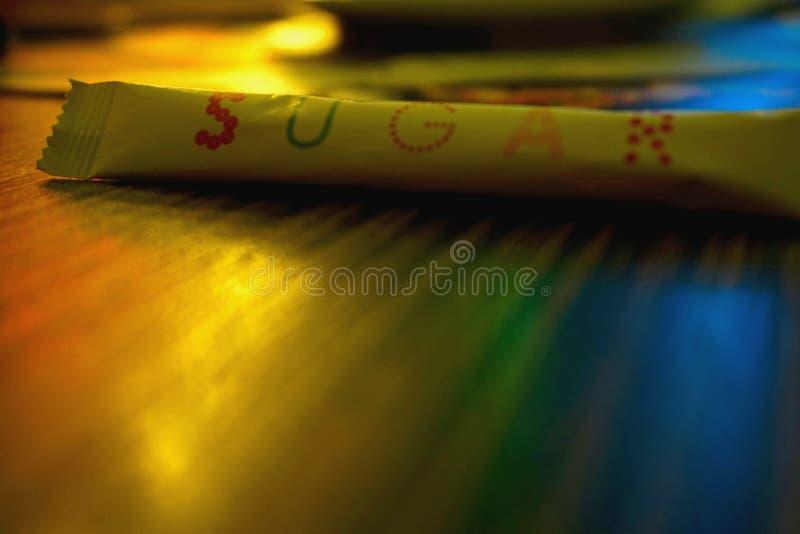被包装的糖,有商标`糖`的香囊 在咖啡馆的五颜六色的照明设备:黄色,蓝色,绿色,橙色 库存图片
