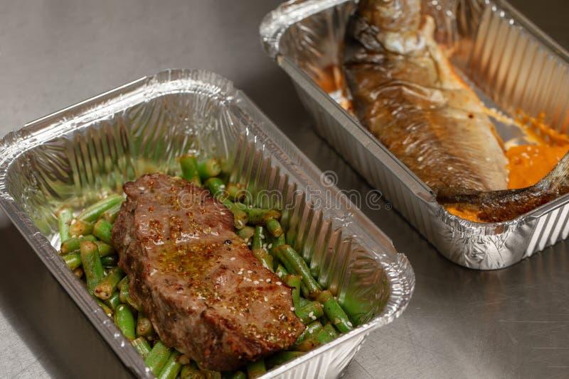 被包装的饭食准备好为去掉或食物交付 吃概念背景的红肉或白色鱼-发牢骚与绿色的臀部的牛排 免版税图库摄影
