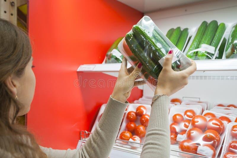 被包装的黄瓜用妇女手在超级市场 免版税库存照片
