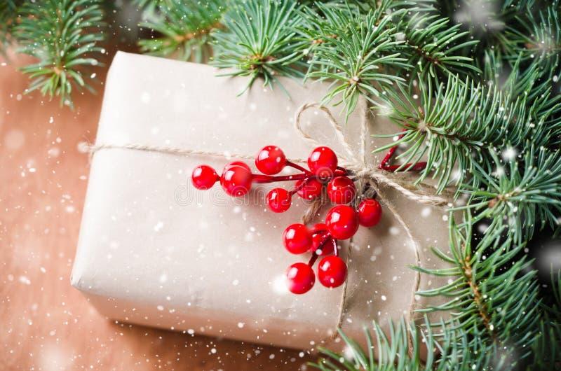 被包裹的圣诞节礼物,毛皮树枝,在土气木背景的红色莓果 拉长的雪作用 库存照片