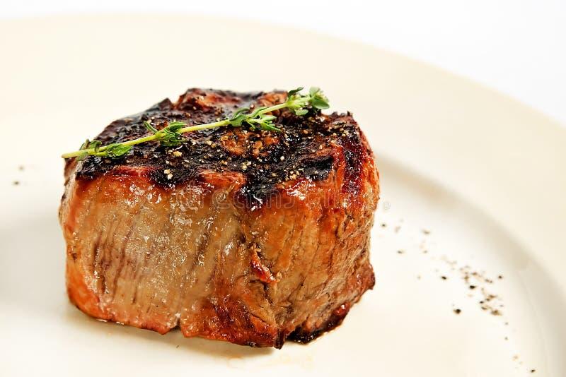 被包裹的烟肉牛肉最佳的烹调内圆角新查出的可爱的牛至准备好的迷迭香贤哲牛排白色 免版税库存图片