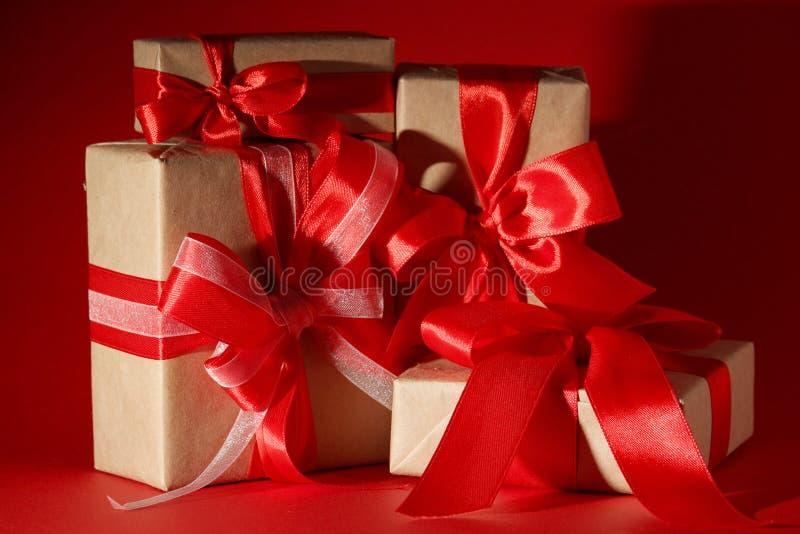 被包裹的礼物有与拷贝空间的明亮的红色背景 免版税库存图片