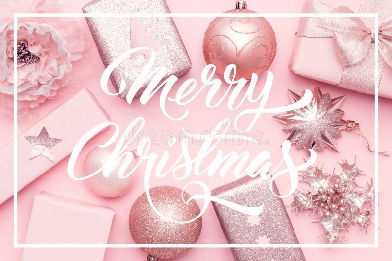 被包裹的xmas箱子、圣诞节装饰品和中看不中用的物品 在粉红彩笔背景隔绝的桃红色圣诞节礼物 免版税库存照片